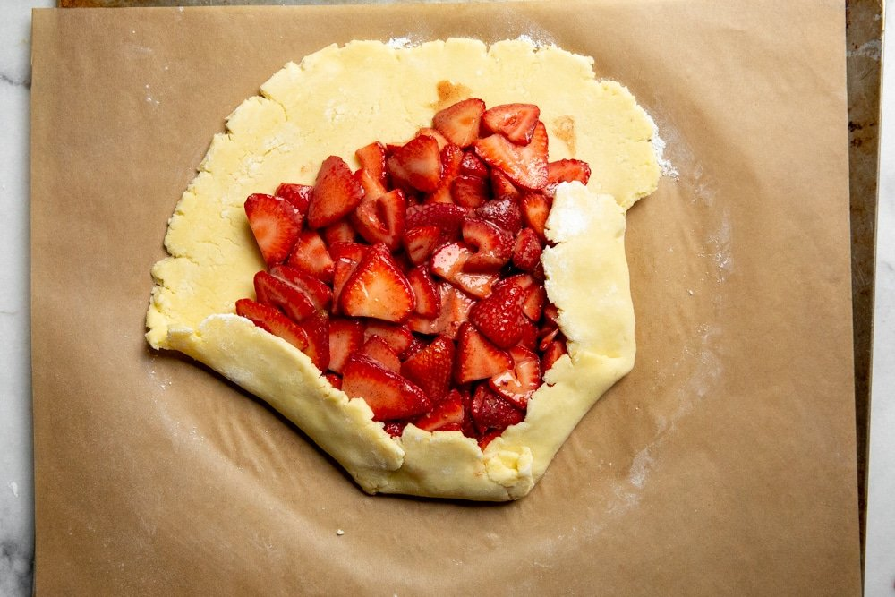 Process shot showing how to fold up the pie dough for the strawberry galette recipe.