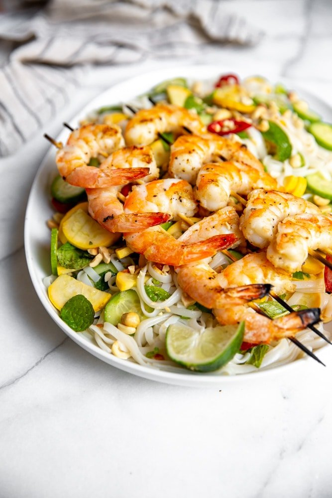 Side angle shot of the Vietnamese rice noodle salad on a platter topped with grilled shrimp.