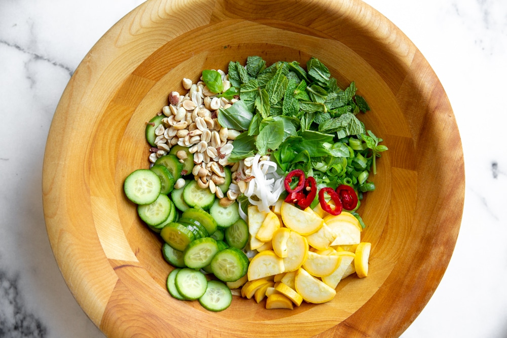 Process shot showing the ingredients for the Vietnamese rice noodle salad arranged in a large bowl before tossing.