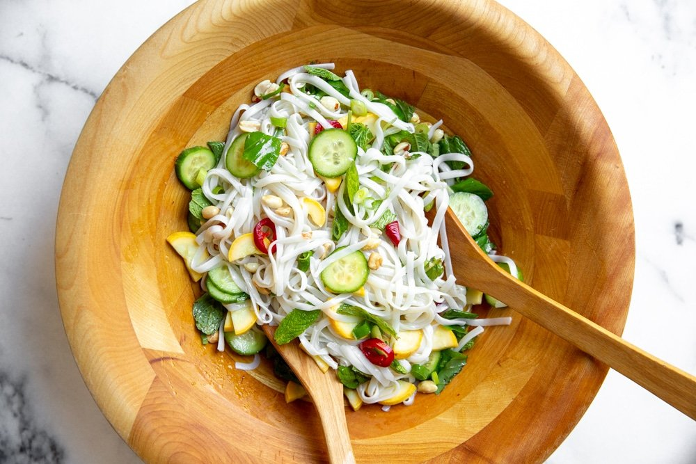 Process shot showing the rice noodle salad in a large bowl after tossing.