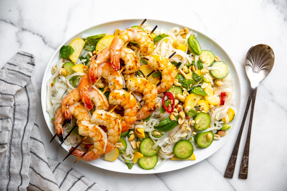 Rice noodle salad with shrimp on a platter, with serving spoons alongside.