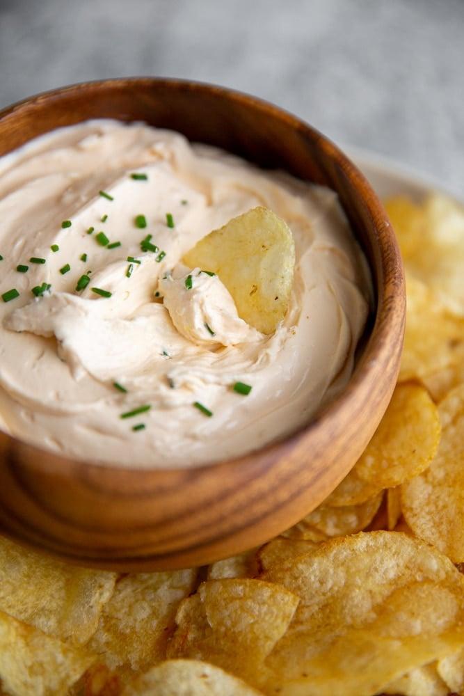 Close up of a potato chip dipping into a bowl of sriracha cream cheese dip.