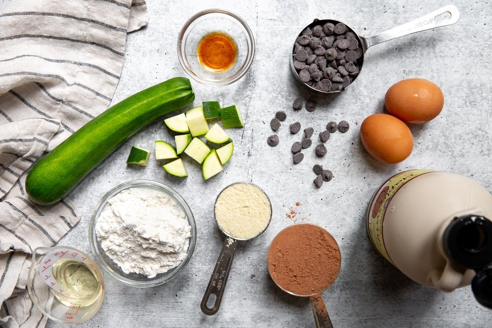 All of the ingredients for the healthy zucchini brownies arranged on a work surface.
