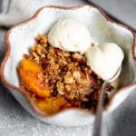 Gluten free peach crisp in a serving bowl with vanilla ice cream.