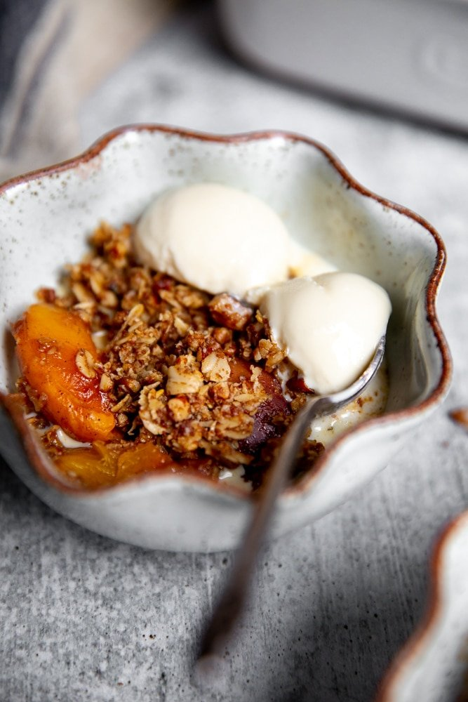 Close up of a bowl of gluten free peach crisp topped with vanilla ice cream.