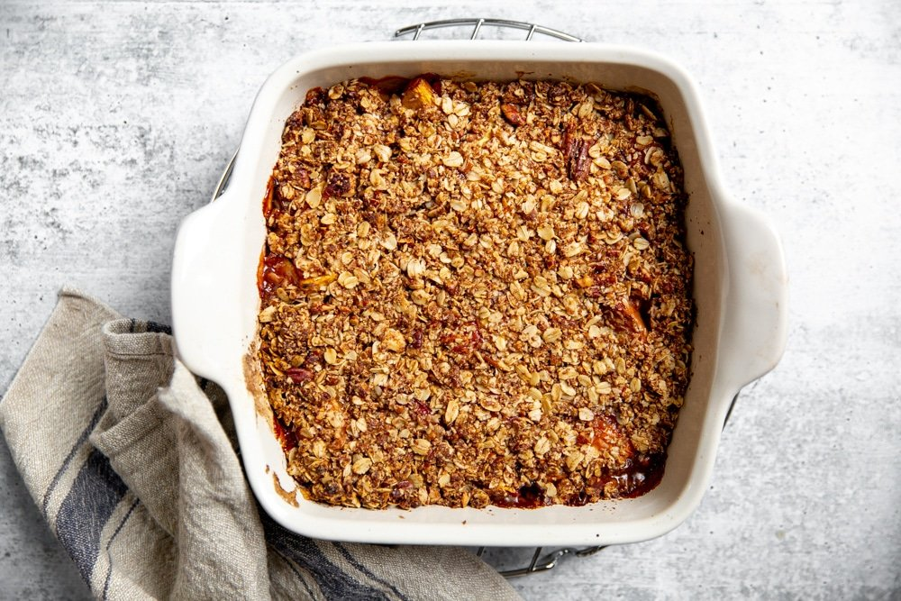Baked peach crisp in a baking dish on a cooling rack.