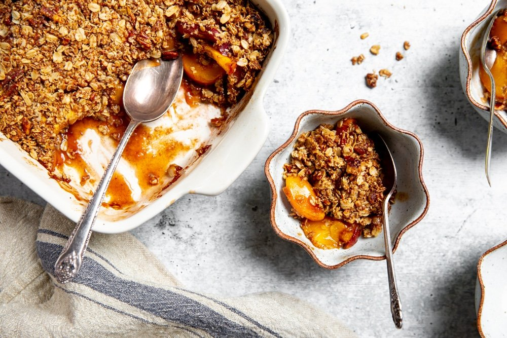 Overhead shot of gluten free peach crisp in serving bowls.