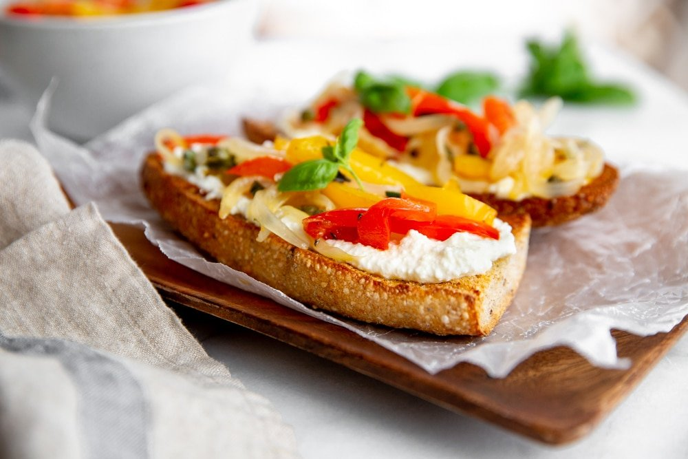 Peppers and onions on toasted baguette halves with ricotta cheese.