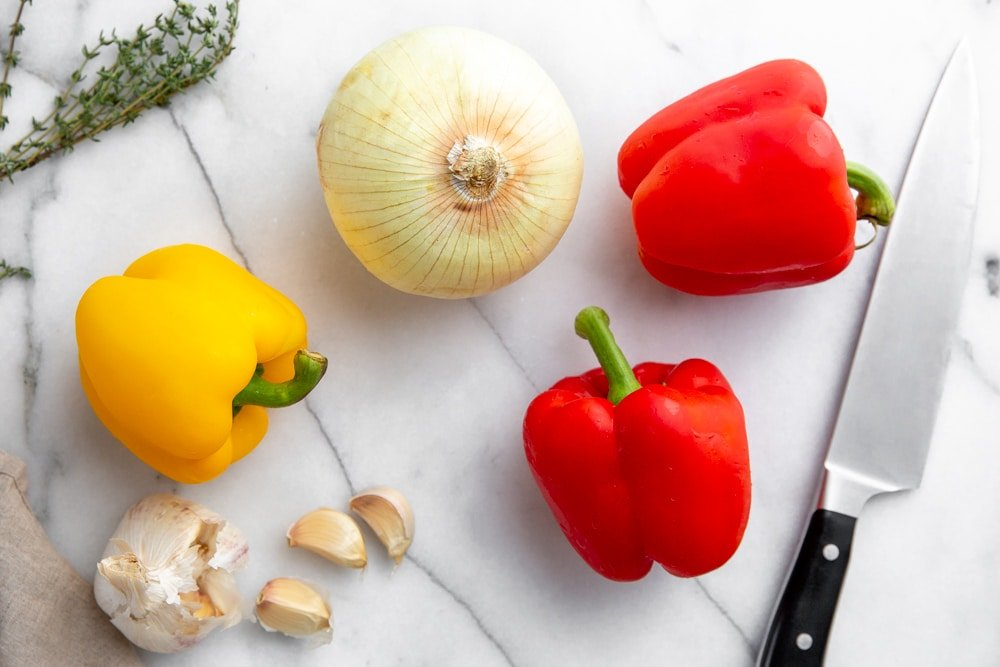 Bell peppers, onion, garlic cloves and thyme on a countertop.