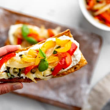 Hand holding a toasted baguette topped with ricotta and roasted peppers and onions.