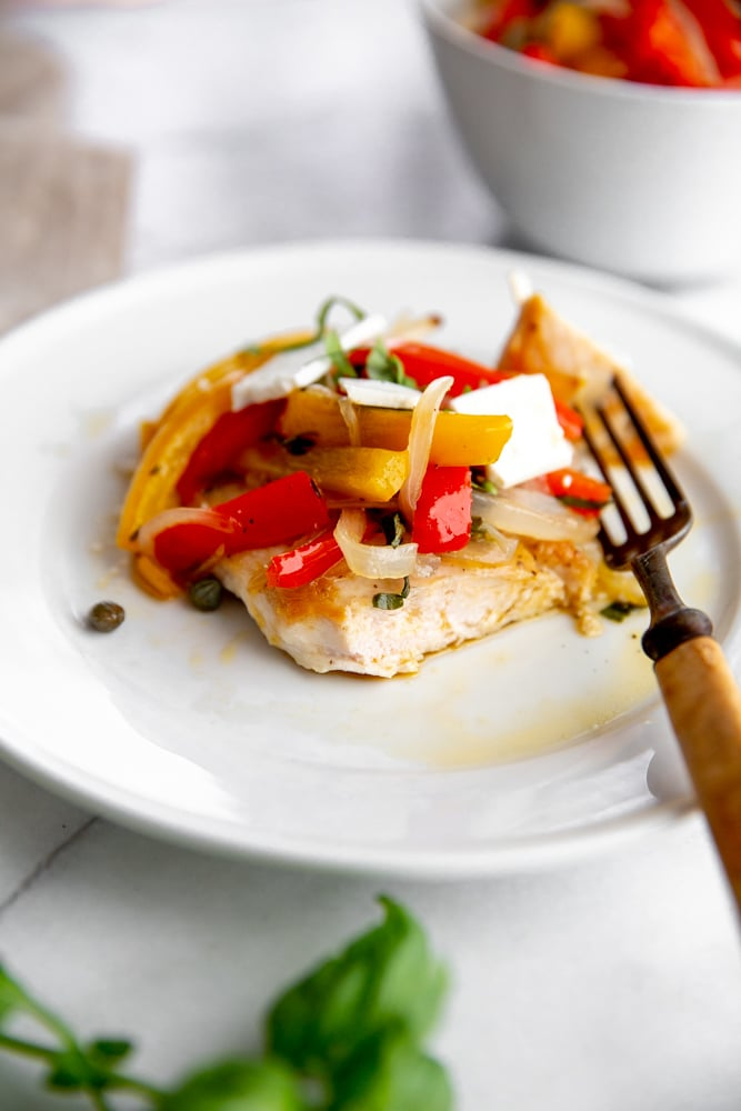 Roasted peppers over a cooked chicken breast, topped with feta cheese