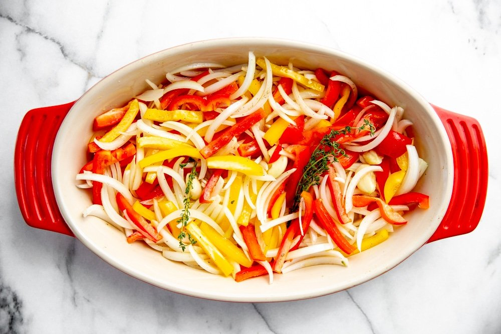 Process shot showing sliced peppers and onions in a baking dish before baking.