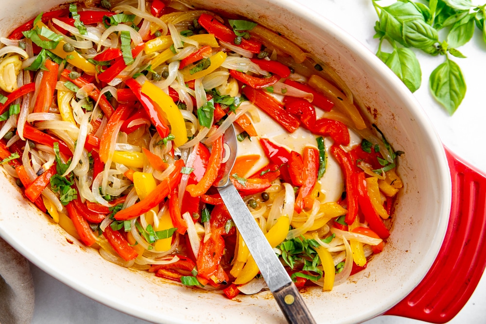 Close up of roasted peppers and onions in a baking dish with a spoon.