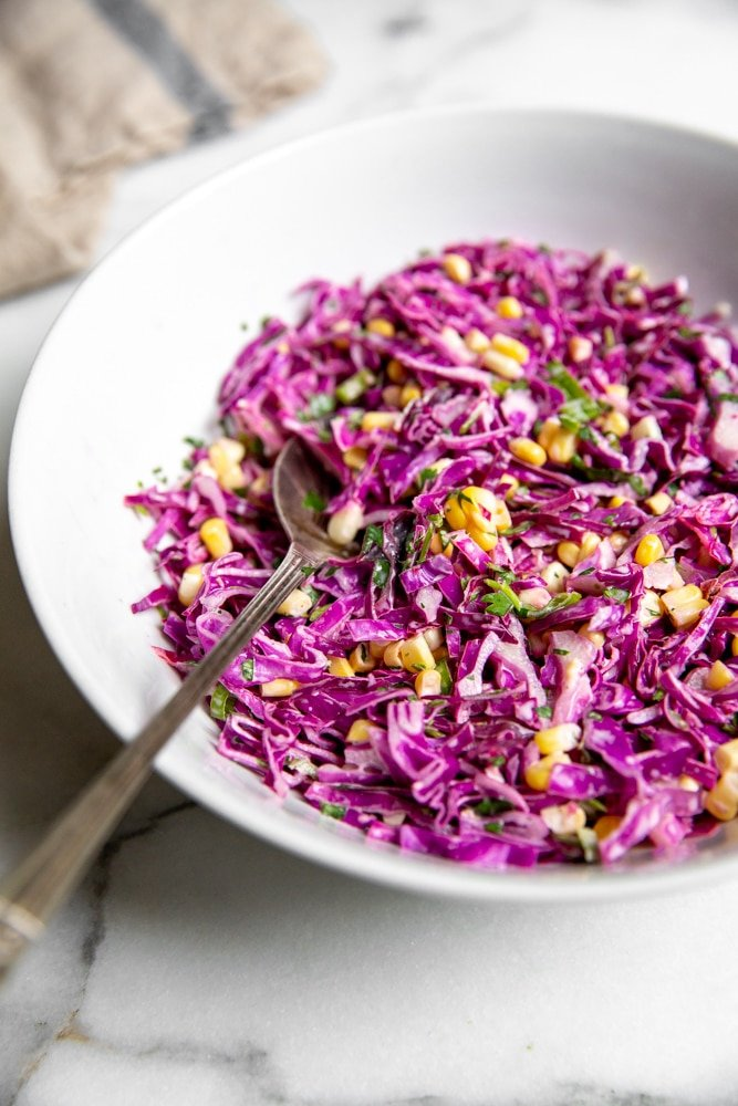 Close up side view of the red cabbage and corn slaw in a bowl.