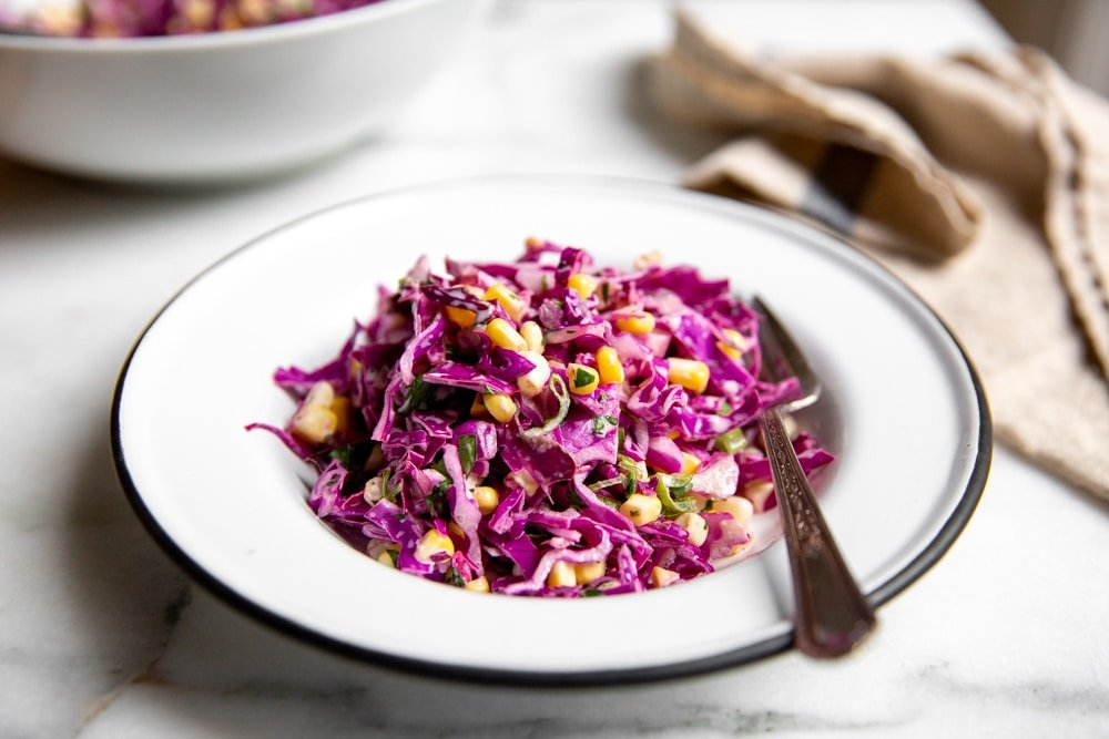 Cabbage and corn coleslaw in a serving bowl with a fork.