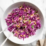 Red cabbage coleslaw in a bowl with serving spoons.