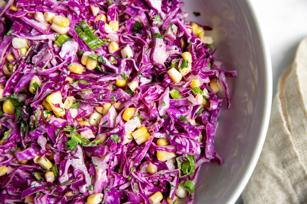 Overhead close up of red cabbage slaw in a serving bowl.