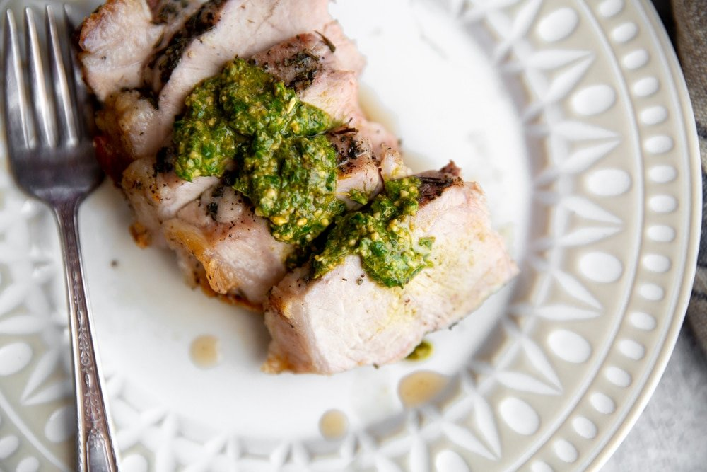 Overhead close up of a sliced pork chop on a plate drizzled with green sauce.