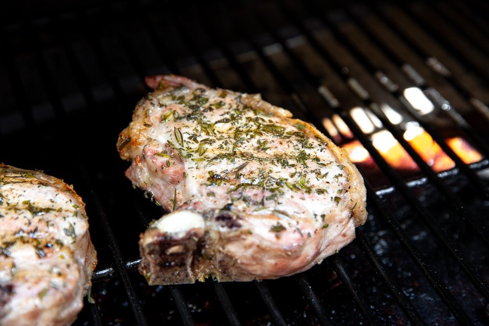Process shot showing bone in pork chops cooking on a Traeger grill.