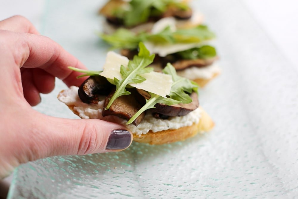 Hand grabbing a ricotta crostini topped with mushrooms and arugula.