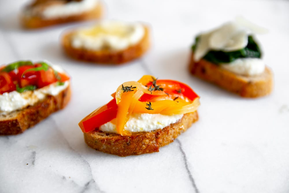 Close up of ricotta crostini topped with peppers and onions.
