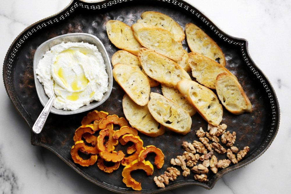 Overhead shot of tray with whipped ricotta, crostini, squash and walnuts.