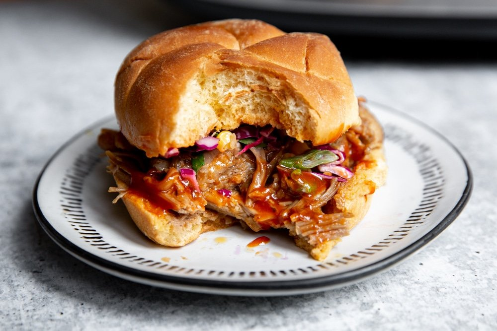 Close up of a bbq pork sandwich with a bite taken out.