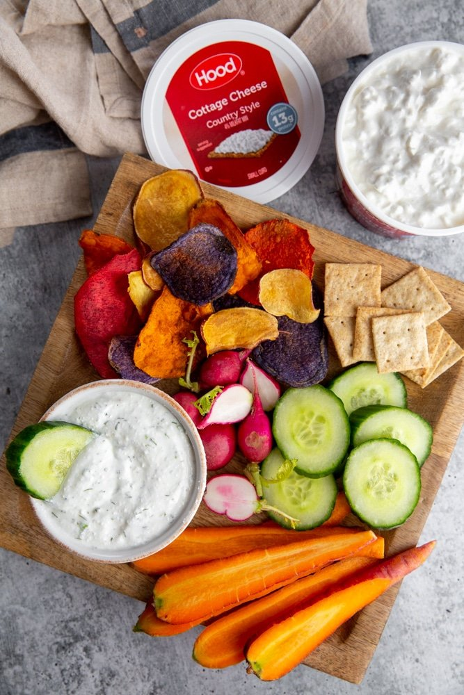 The creamy veggie dip on a serving board with sliced veggies and crackers, with a container of cottage cheese alongside.