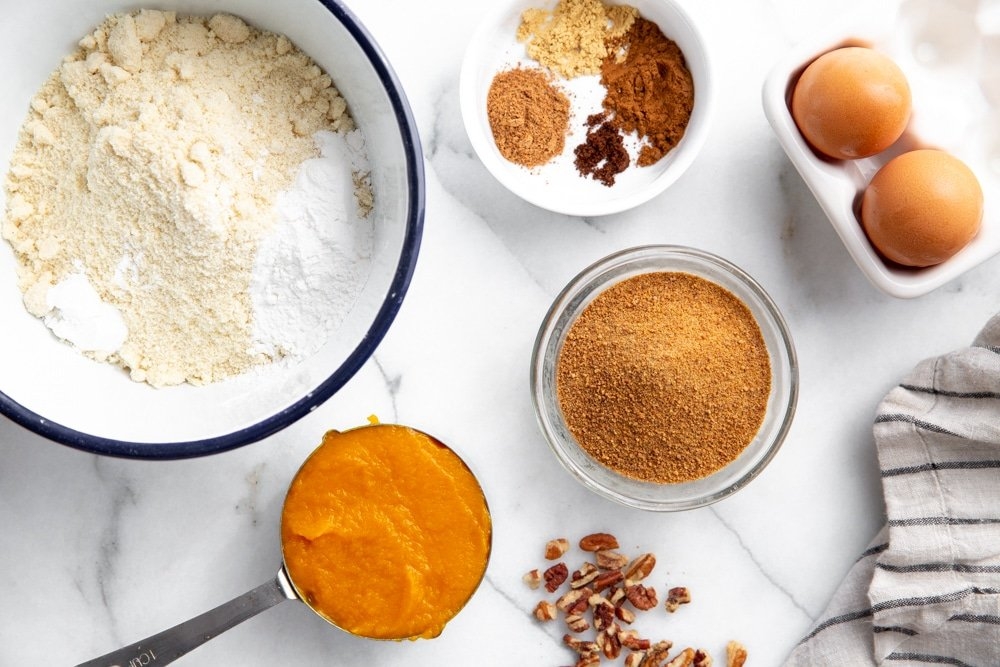 All of the ingredients for the healthy pumpkin bread arranged on a marble surface.