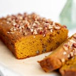 Close up of a loaf of healthy pumpkin bread on a serving board.