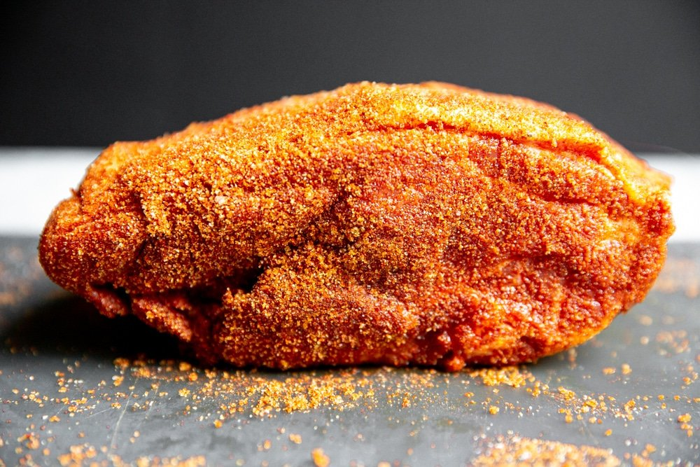 Pork shoulder coated in the spice rub, on a cutting board.
