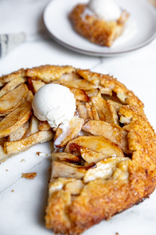 A gluten free apple galette on a marble surface topped with ice cream.