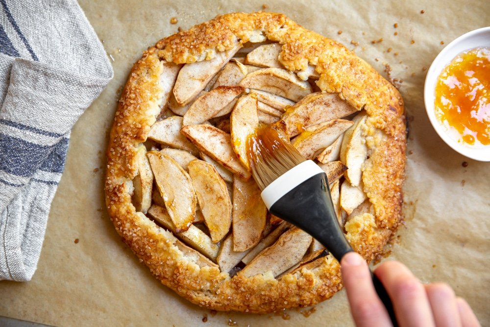Hand brushing warm apricot jam over the apples in the baked galette.