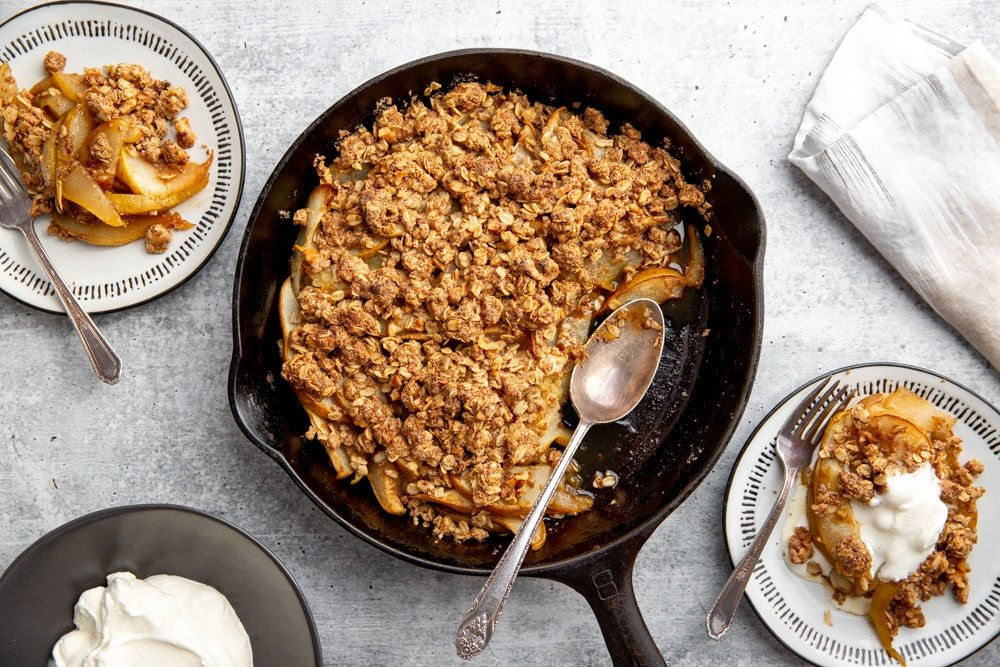 Gluten free pear crumble in a cast iron skillet, with serving plates alongside.