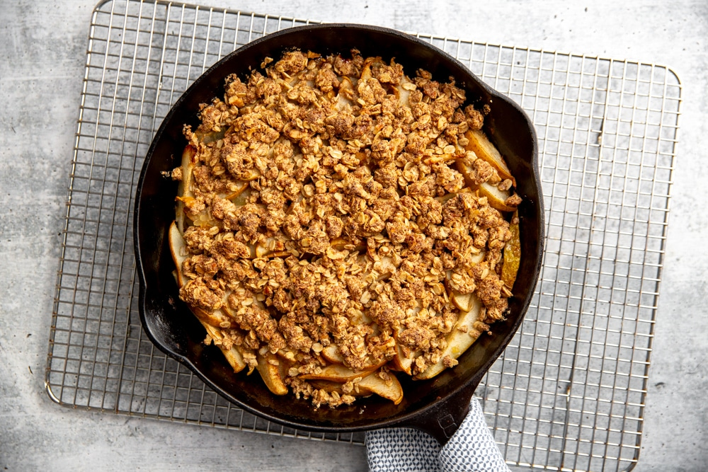 A baked pear crumble in a cast iron skillet, cooling on a rack.