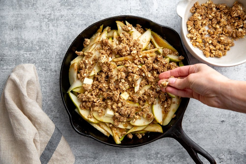 Process shot showing a hand sprinkling gluten free crisp topping over pears in a cast iron skillet.