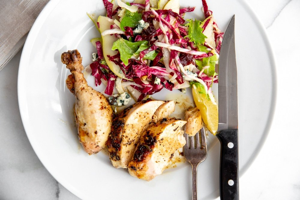 Roast chicken and salad on a plate with a fork and knife.