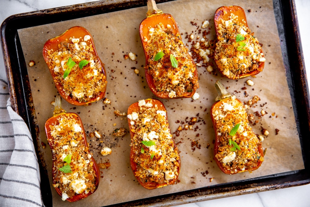 Baked lamb stuffed squash on a parchment lined baking sheet.