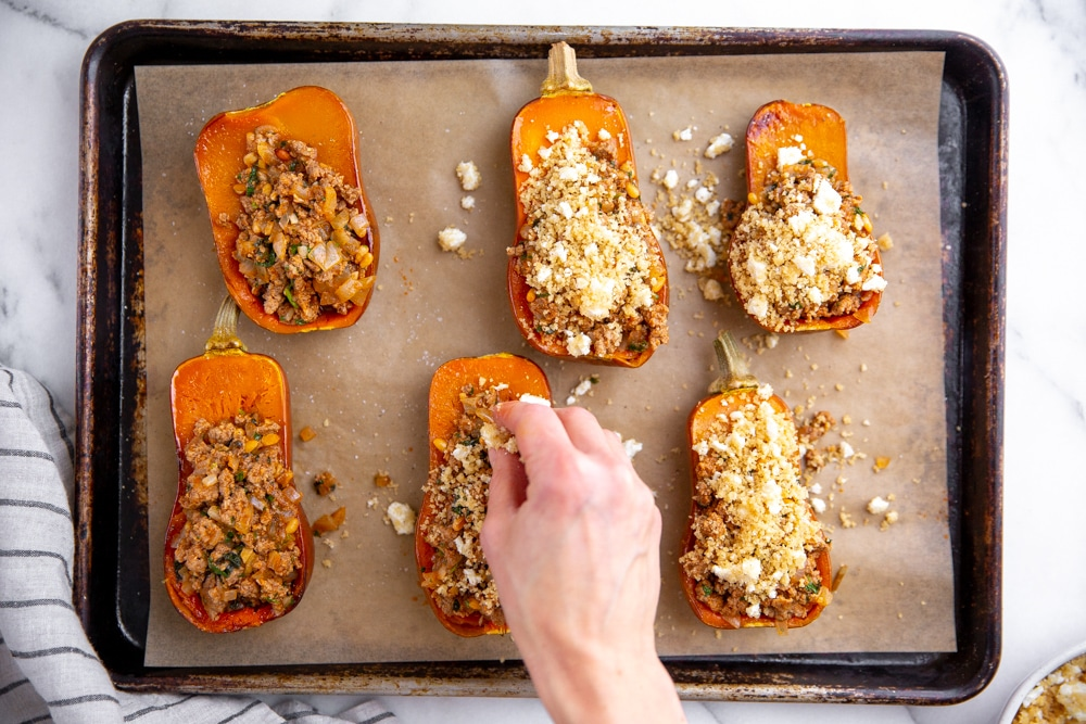 Hand sprinkling the breadcrumb topping over the stuffed squash.