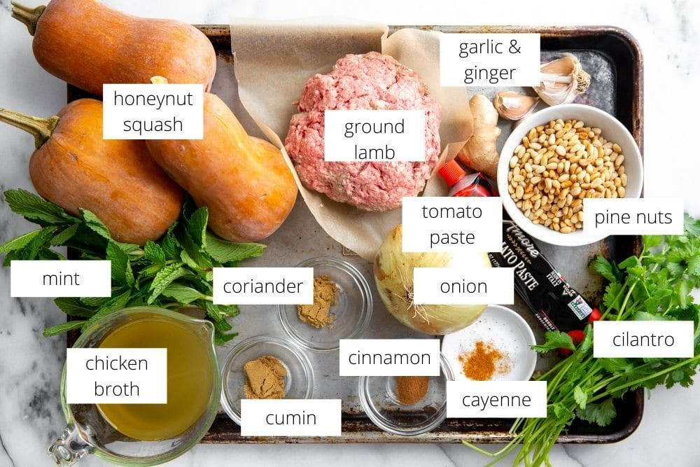 All of the ingredients for the lamb stuffed squash arranged on a sheet pan.