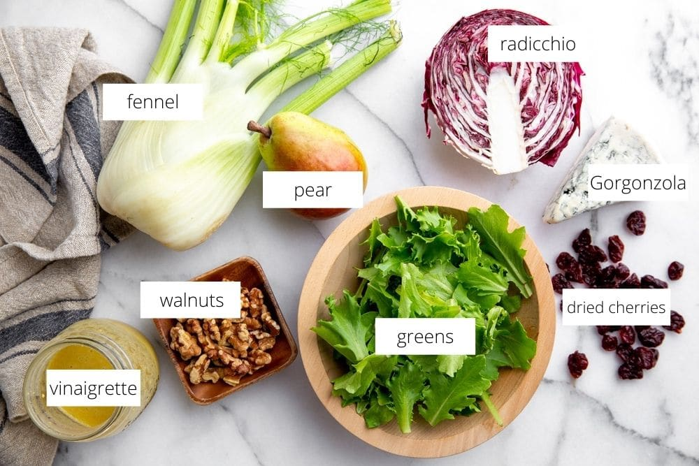 All of the pear salad recipe ingredients arranged on a marble surface.