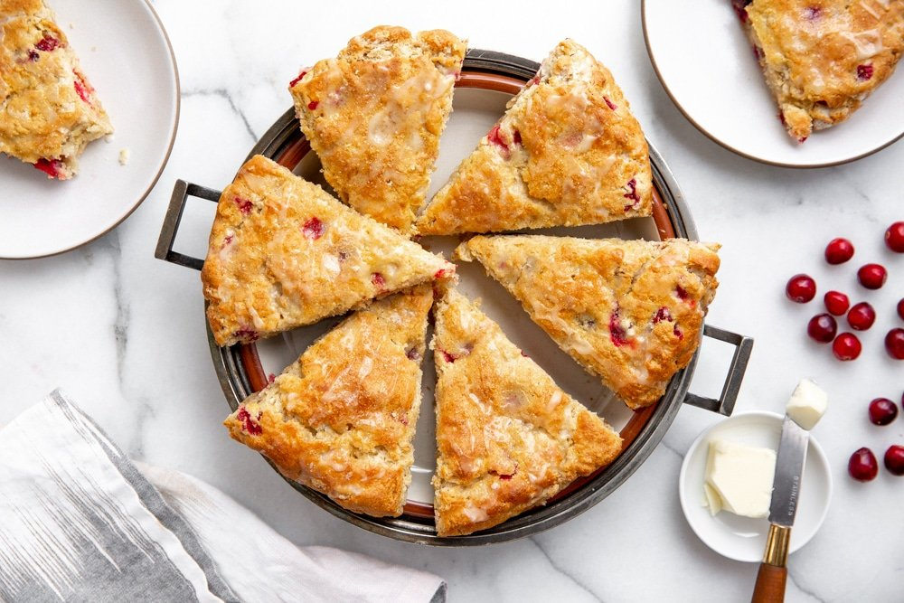Cranberry Scones on a serving platter with plates and butter alongside.