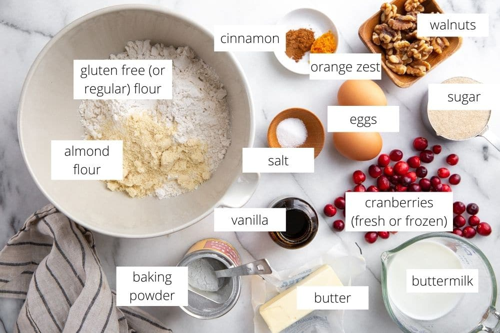 All of the ingredients for the cranberry scones recipe arranged on a marble surface.