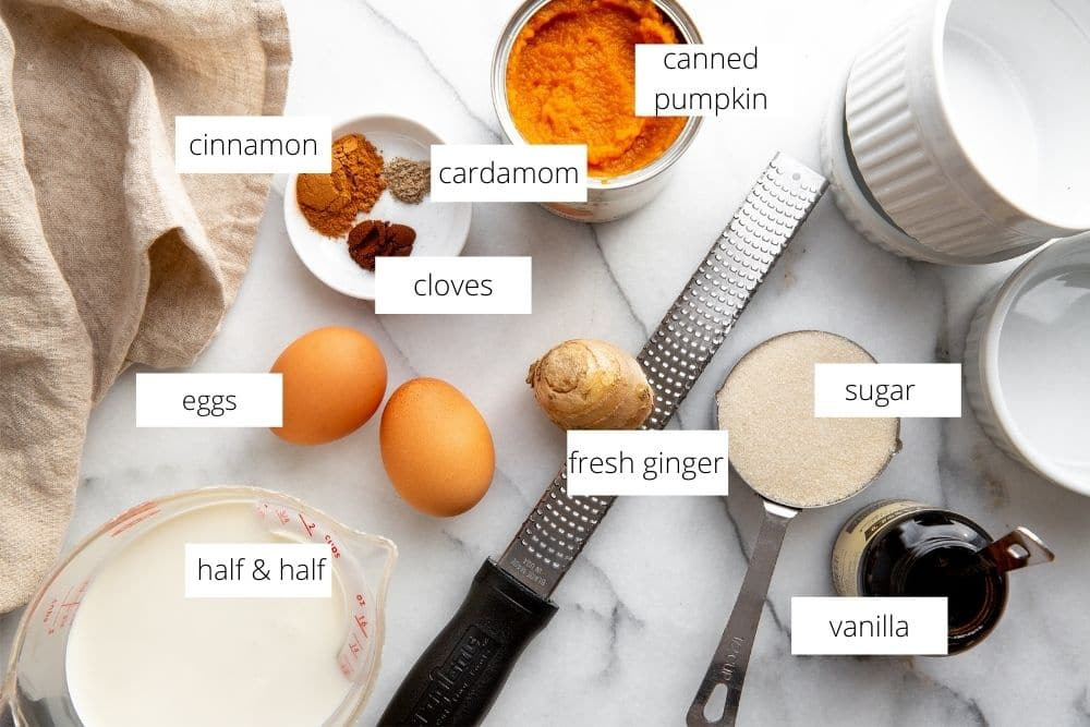 All of the ingredients for the crustless pumpkin pie arranged on a marble work surface.