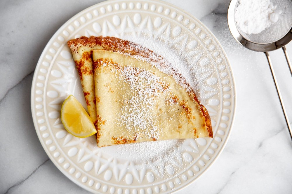 Crepes on a plate dusted with powdered sugar, with a lemon wedge alongside.