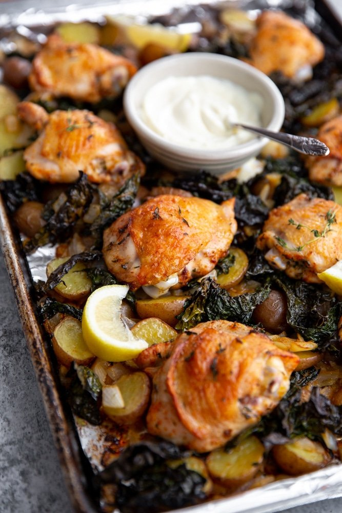 Close up of crispy sheet pan chicken and veggies with a bowl of aioli.