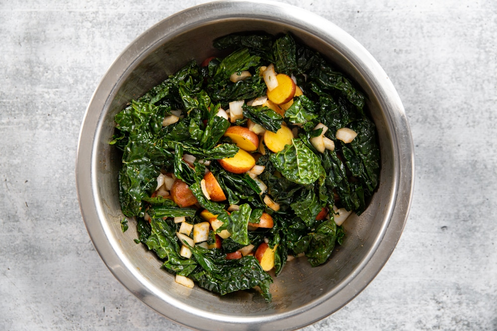 Kale, potatoes, onion, garlic and thyme in a large mixing bowl.