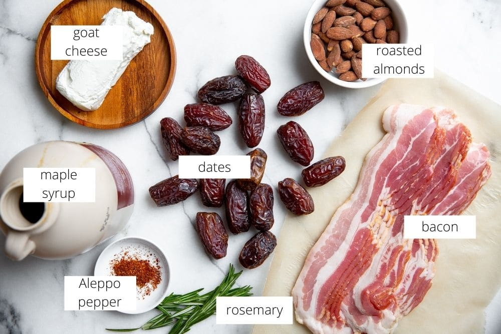 All of the ingredients for the devils on horseback recipe arranged on a marble surface.