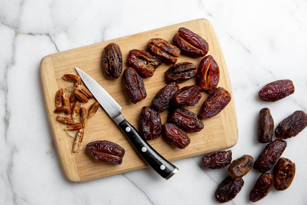 Medjool dates on a cutting board with a small knife alongside, showing how to remove the pits.