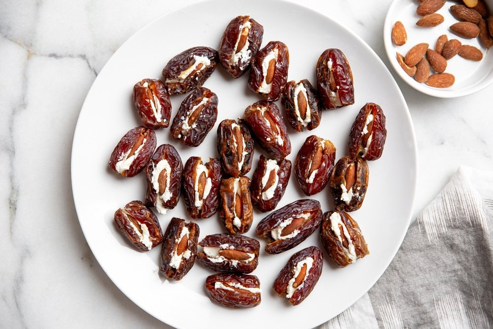 Process shot showing the goat cheese and almond stuffed dates on a plate for the devils on horseback recipe.